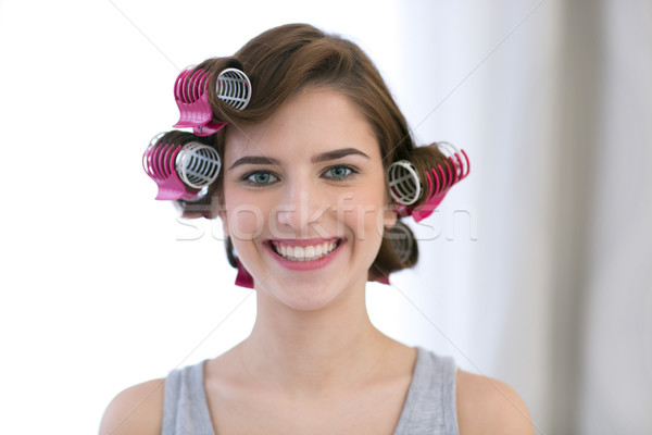Portrait of a smiling woman with curlers on her head Stock photo © deandrobot