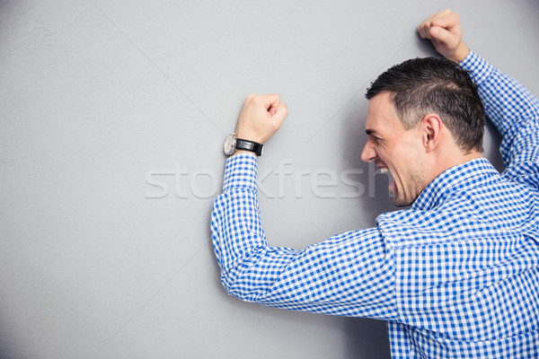 Angry man hitting wall Stock photo © deandrobot