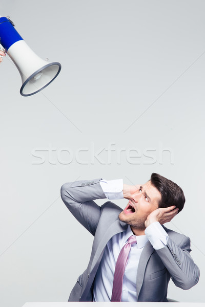 Businessman covering his ears from megaphone  Stock photo © deandrobot