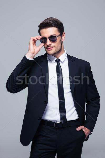 Portret trendy om de afaceri ochelari de soare în picioare gri Imagine de stoc © deandrobot