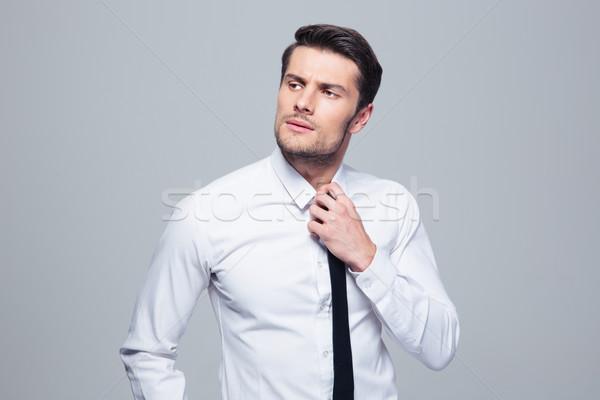 Pensive businessman straightening his tie Stock photo © deandrobot