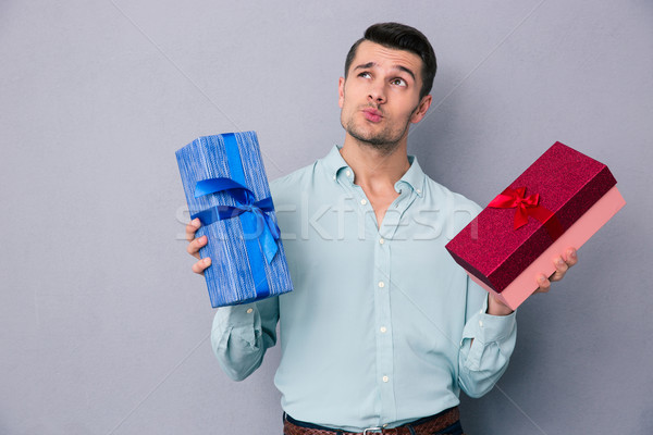 Pensive young man holding two gift box Stock photo © deandrobot