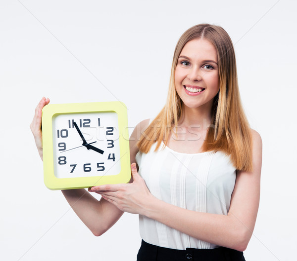 Smiling businesswoman holding big clock Stock photo © deandrobot