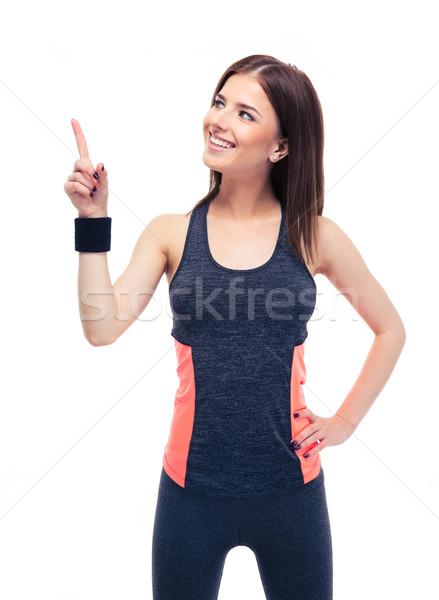 Piękna kobieta fitness odzież sportowa wskazując w górę szczęśliwy Zdjęcia stock © deandrobot