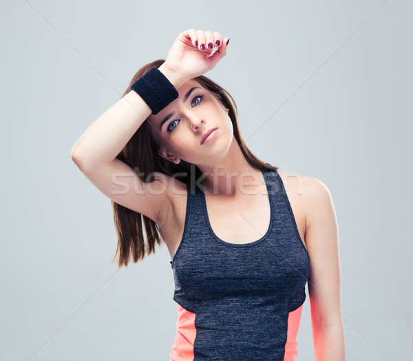 Fitness woman wipes the sweat from his brow Stock photo © deandrobot