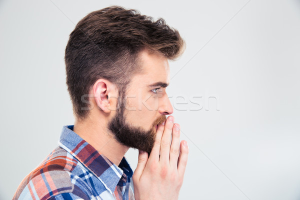 Side view protrait of a casual man praying Stock photo © deandrobot