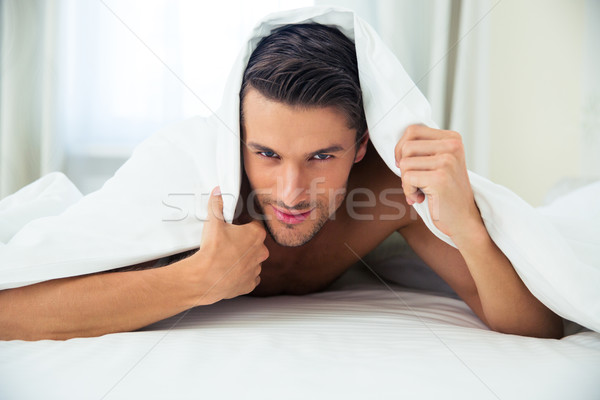 Handsome man lying under blanket in the bed Stock photo © deandrobot