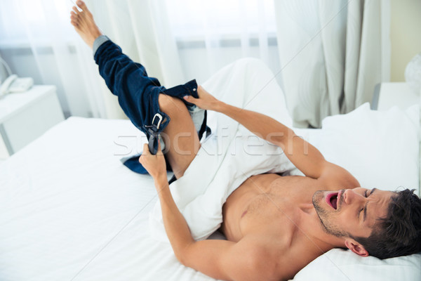 Man waking up and dressing jeans Stock photo © deandrobot