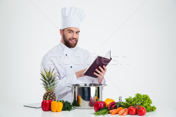 Male chef cook holding recipe book and preparing food Stock photo © deandrobot