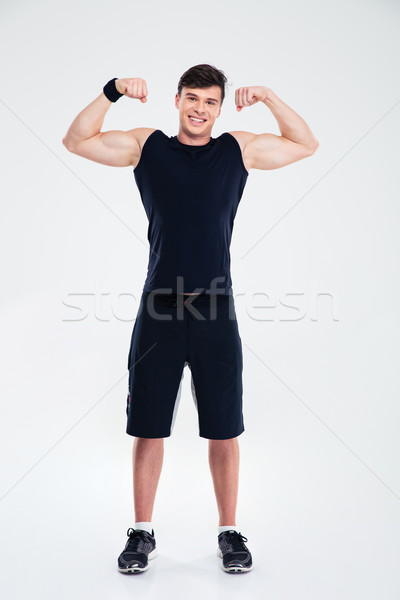 Full length portrait of a smiling man showing his biceps  Stock photo © deandrobot