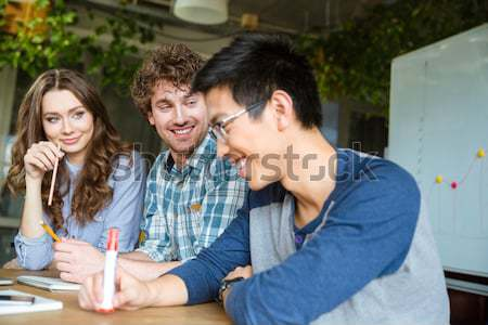 Smiling curly man using cellphone while his friends studying  Stock photo © deandrobot