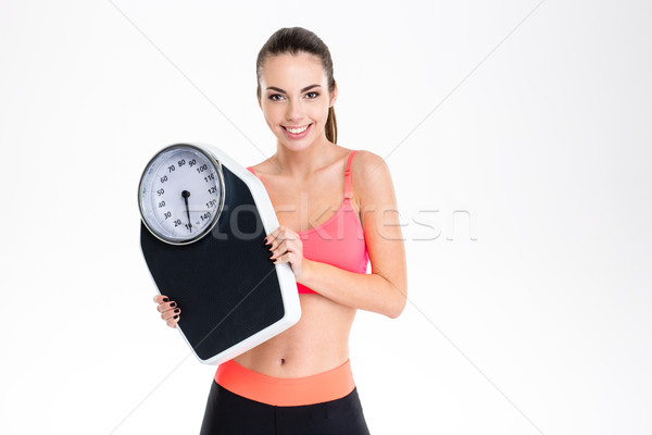 Smiling positive young fitness woman in sportwear holding weighing scale Stock photo © deandrobot