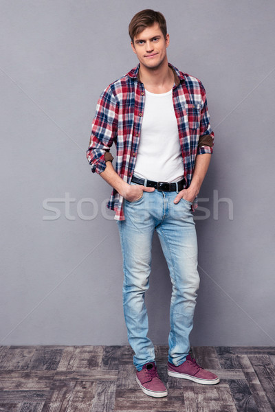 Full length portrait of handsome confident  man in checkered shirt Stock photo © deandrobot