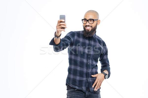 Cheerful african american man with beard smiling and taking selfie Stock photo © deandrobot