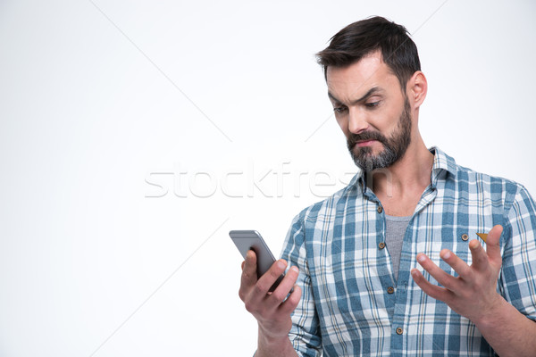 Stock photo: Angry man holding smartphone