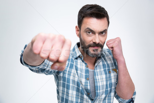 Handsome man punching with fist at camera Stock photo © deandrobot