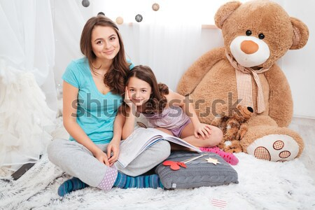 Two cute smiling sisters sitting and drawing together Stock photo © deandrobot