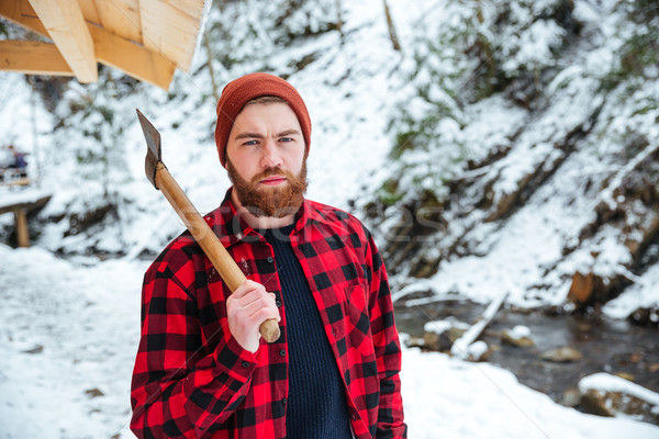 Serious bearded young lumberjack with axe at mountains in winter Stock photo © deandrobot