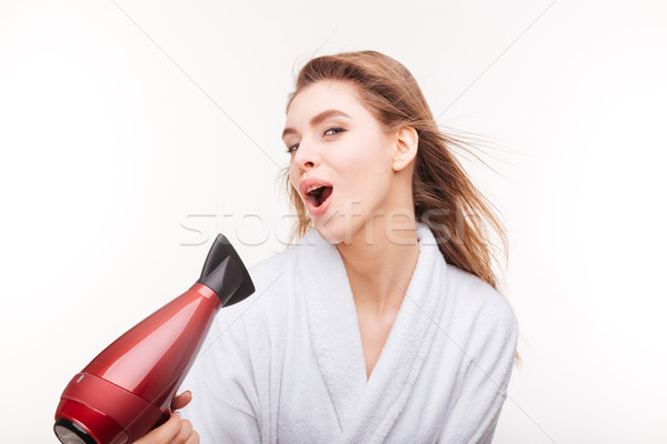 Playful cute woman singing and drying her hair with dryer Stock photo © deandrobot