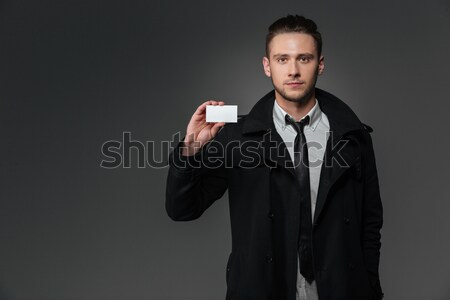 Businessman in black coat standing and holding blank business card Stock photo © deandrobot