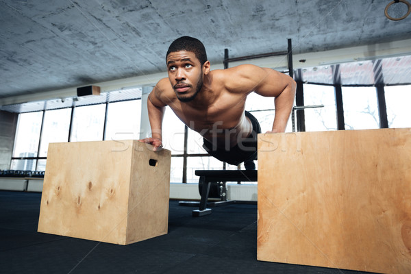 Healthy fitness man doing push-ups in the gym  Stock photo © deandrobot