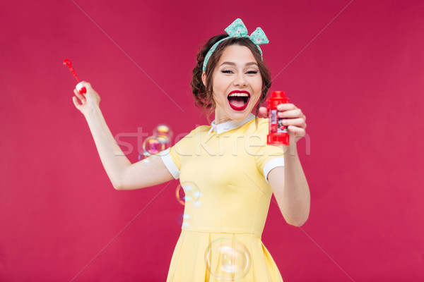 Happy excited pinup girl blowing soap bubbles and laughing Stock photo © deandrobot