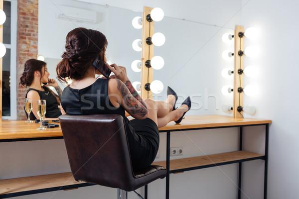 Nő ül beszél mobiltelefon öltöző hátulnézet Stock fotó © deandrobot
