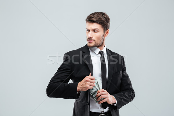 Serious businessman in suit and tie hiding money in pocket Stock photo © deandrobot
