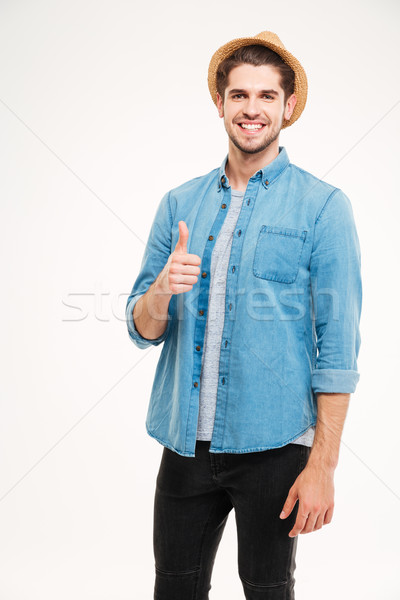 Cheerful young man showing thumbs up Stock photo © deandrobot