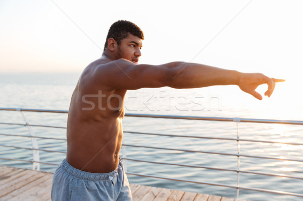 Shirtless african man athlete working out and pointing away Stock photo © deandrobot