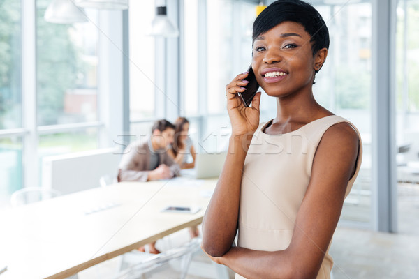 Happy businesswoman standing in office and talking on cell phone Stock photo © deandrobot