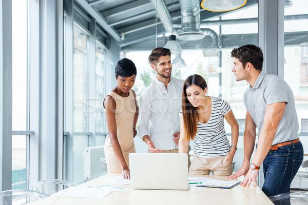 Happy business people creating presentation with laptop in office Stock photo © deandrobot