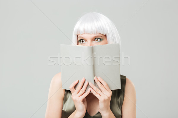 Scared pretty young woman covered her face with book Stock photo © deandrobot