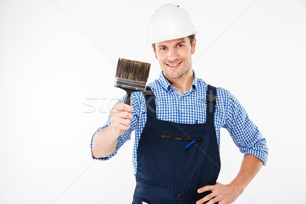 Smiling male painter holding paint brush Stock photo © deandrobot