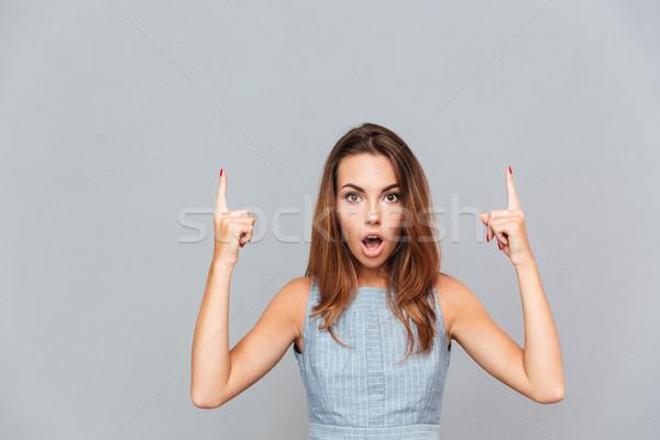Maravilhado mulher jovem indicação para cima tanto Foto stock © deandrobot