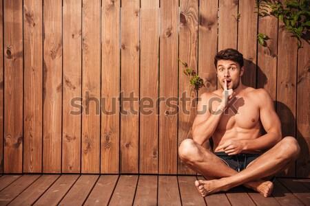 Fiatal jóképű mosolyog férfi fürdőruha ül Stock fotó © deandrobot
