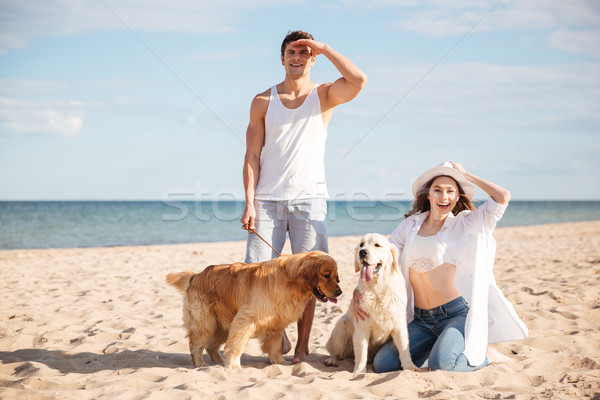 Young beautiful couple standing on the sea shore with dog Stock photo © deandrobot
