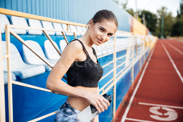 Young sportswoman with bottle of water leaning on the railing Stock photo © deandrobot