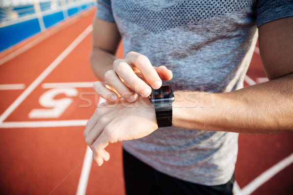 Cropped image of a young muscular man adjusting smart watch Stock photo © deandrobot