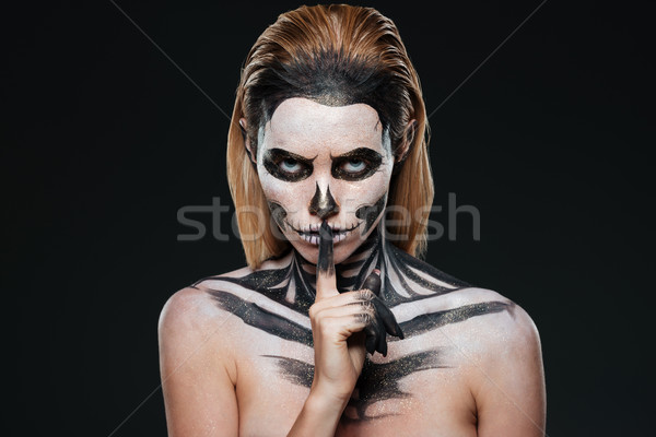 Portrait of woman with gothic skeleton makeup showing silence gesture Stock photo © deandrobot