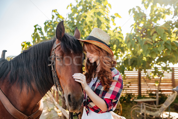 Happy young woman cowgirl standing with her horse on ranch Stock photo © deandrobot