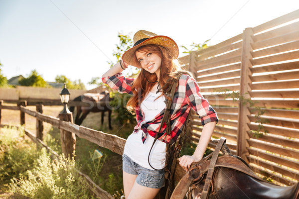 Happy beautiful young woman cowgirl in hat on ranch Stock photo © deandrobot