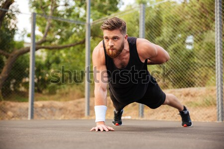Handsome fitness man doing push-up exercises with sport equipment Stock photo © deandrobot