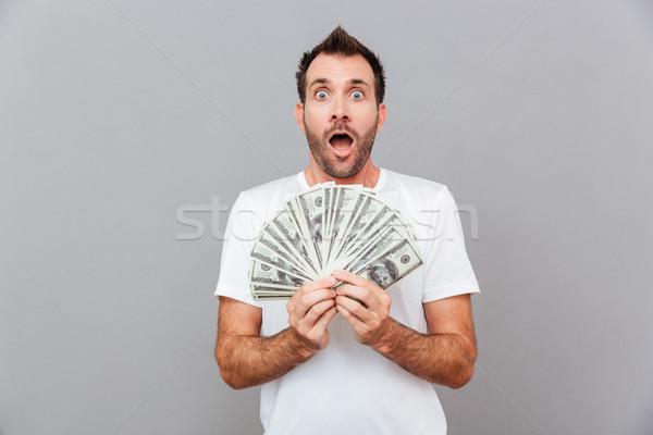 Happy casual man holding bills of US dollars Stock photo © deandrobot