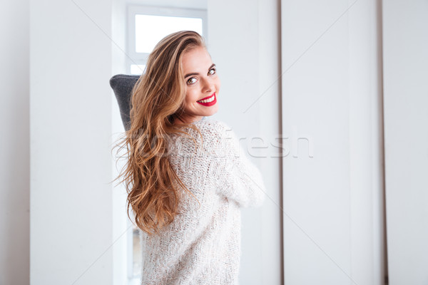 Happy young woman fighting with pillow Stock photo © deandrobot