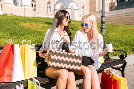 две женщины сидят за пределами глядя довольно обувь Сток-фото © deandrobot