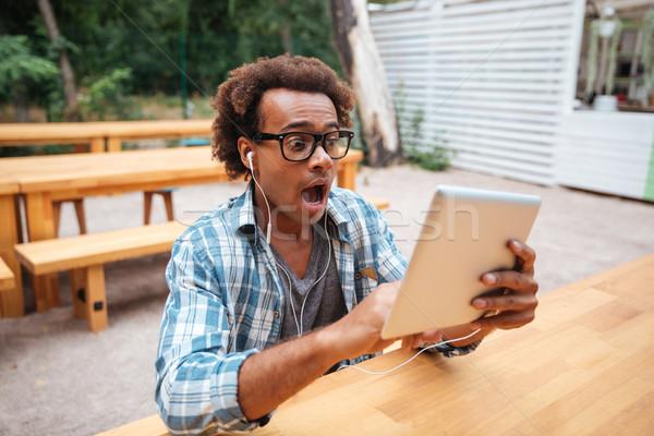 Meglepett afrikai fiatalember tabletta kiált kint Stock fotó © deandrobot