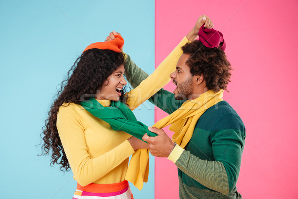 Stock photo: Angry mad african couple in hats and scarves arguing