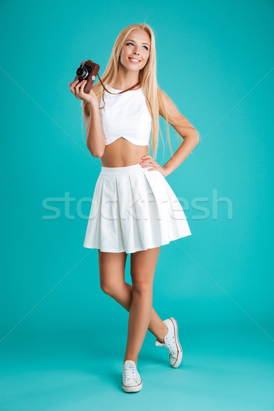 Smiling young woman holding retro camera and looking away Stock photo © deandrobot