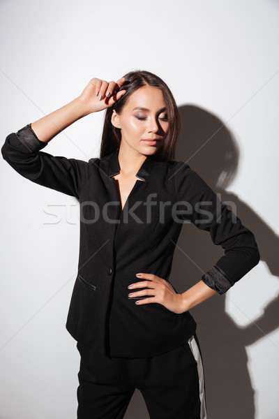 Smart attractive woman in black suit standing with eyes closed Stock photo © deandrobot